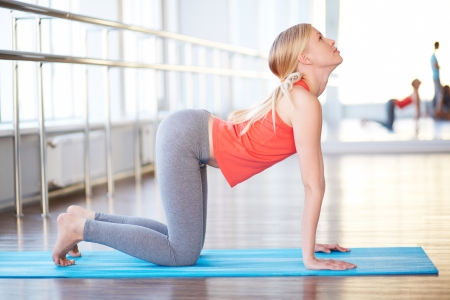 back exercise: Portrait of happy young woman doing exercise for back in gym Stock Photo