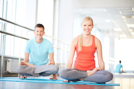 Portrait of healthy girl and guy doing exercise for relaxation in gym photo