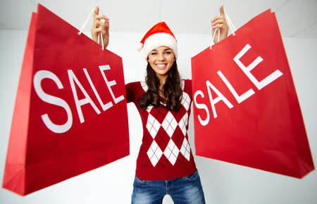 Happy girl in Santa cap holds red paperbags with symbol of sale Stock Photo - 23254783