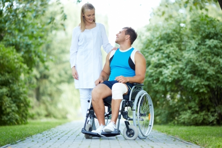 Pretty nurse walking with male patient in a wheelchair in park Stock Photo