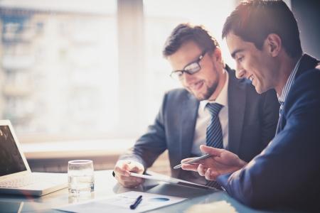 Beeld van twee jonge ondernemers met behulp van het touchpad op de vergadering van Stockfoto