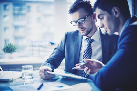business: Bild av två unga affärsmän diskutera projekt vid mötet Stockfoto