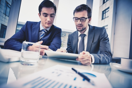 business project: Image of two young businessmen discussing document in touchpad at meeting Stock Photo