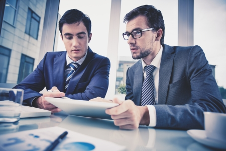 corporate meeting: Image of two young businessmen discussing document in touchpad at meeting Stock Photo