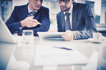 Beeld van twee jonge ondernemers bespreken document in touchpad op het voldoen Stockfoto