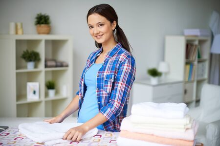 Portrait of happy housewife looking at camera while folding towels at home photo