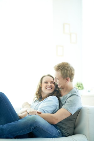 Young man and his girlfriend lying on sofa at home Stock Photo