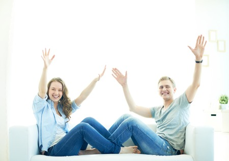 euphoric: Joyful couple sitting on sofa with raised arms and looking at camera