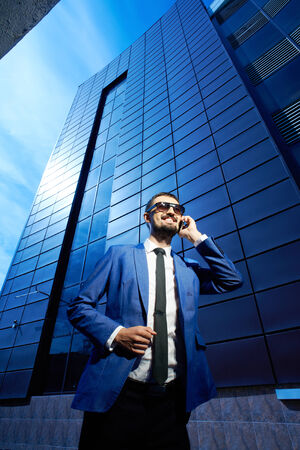 corporate buildings: Vertical image of a smiling businessman speaking on the phone Stock Photo