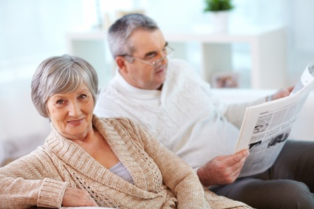 madam: Portrait of mature woman looking at camera on background of her husband reading newspaper Stock Photo