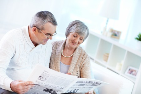 reading a newspaper: Portrait of happy mature couple sitting at home and reading newspaper together