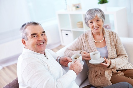 Portrait of mature man and his wife drinking tea at home