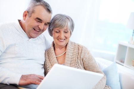 jubilados: Retrato de hombre maduro y su esposa trabajan con ordenador portátil en casa