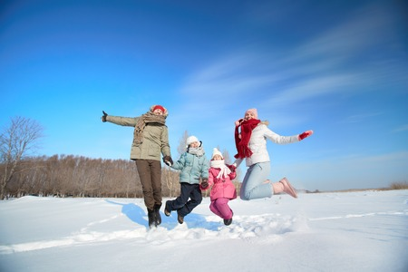 Happy parents and their kids in winterwear having fun outside photo