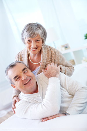 Portrait of a happy senior couple looking at camera with smiles  photo