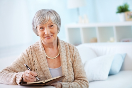 Portrait of aged female with notepad looking at camera with smile photo