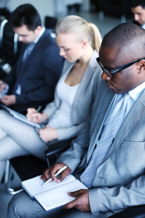 conference meeting: Image of business people sitting in rows and making notes at conference