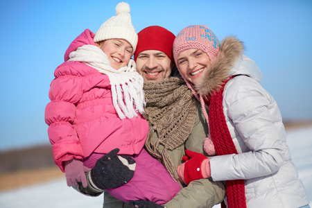 Happy parents and their daughter in winterwear looking at camera with smiles photo