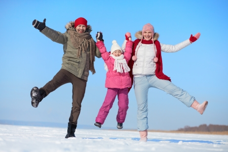 winterwear: Happy parents and their daughter having fun in winter