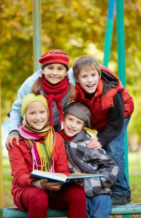 Portrait of happy schoolkids with book looking at camera outdoors photo