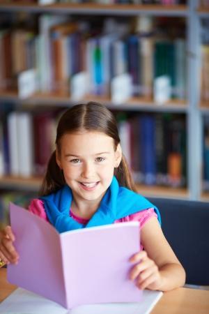 lovely girl: Portrait of a lovely girl reading in library