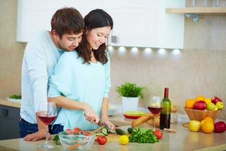 Portrait of young woman cooking salad with her husband near by  photo