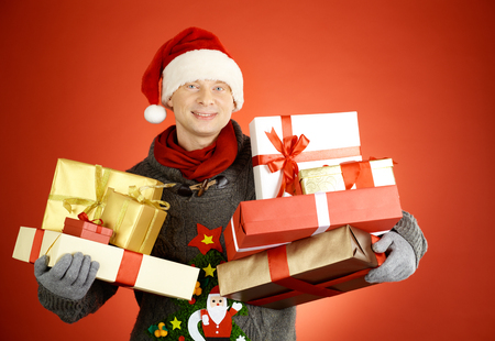 Portrait of happy man in Santa cap with giftboxes looking at camera photo
