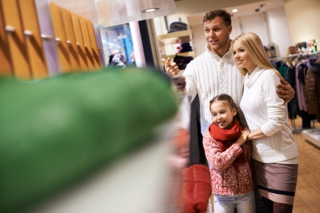 Portrait of modern young couple and their daughter spending time in the mall photo