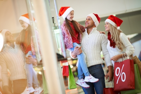 Portrait of happy family in Santa caps on Christmas sale in the mall photo