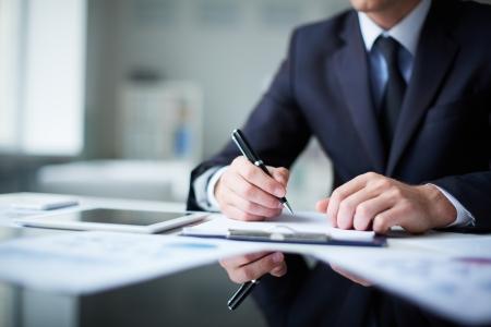 Gros plan sur les mains des hommes avec un stylo sur le document