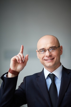 upwards: Portrait of attractive businessman in eyeglasses pointing upwards