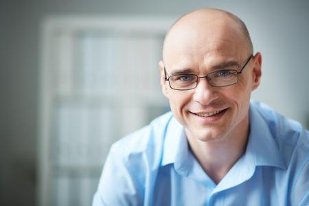 Porträtt av attraktiva affärsman i glasögon tittar på kameran Stockfoto