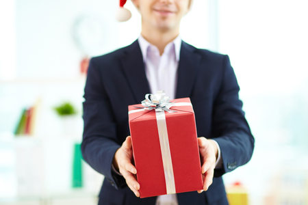 Image of businessman giving present in red giftbox