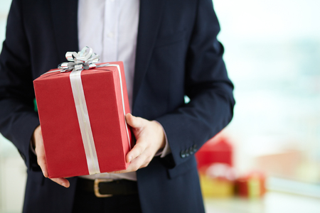 Close-up of businessman holding present in red giftbox photo