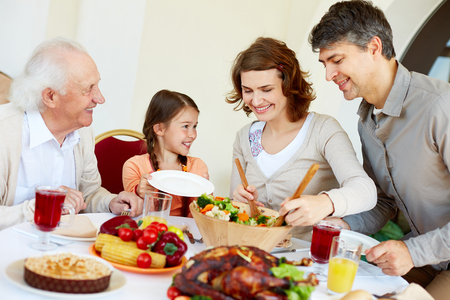 thanksgiving adult: Portrait of happy family sitting at festive table while having Thanksgiving dinner