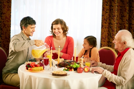 Portrait of happy family sitting at festive table and having Thanksgiving dinner photo