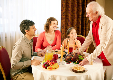 Portrait of happy family sitting at festive table and looking at senior man during Thanksgiving dinner photo