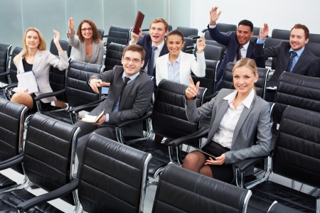 Image of business people sitting in rows at seminar with raised arms photo