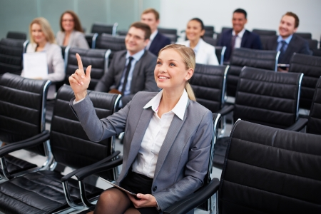 Image of business people sitting in rows at seminar with pretty woman in front raising her arm photo