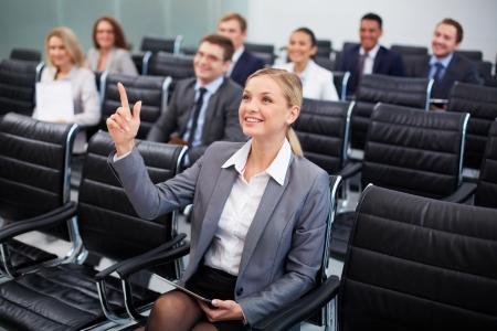 reportero: Imagen de la gente de negocios sentado en filas en el seminario con una mujer bonita delante levantando el brazo