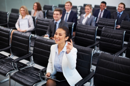 competency: Image of business people sitting in rows at seminar with pretty woman in front raising her arm