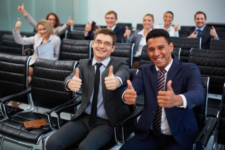 competent: Two happy young businessmen showing thumbs up on background of their colleagues