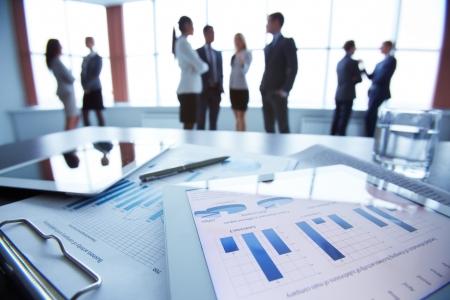 バック グラウンドで対話するオフィス ワーカー、机の上にタッチパッドのビジネス ドキュメントのクローズ アップ 写真素材
