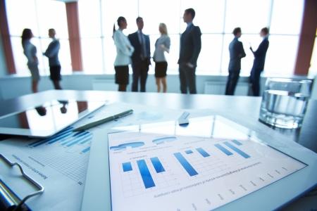 オフィス ワーカーはバック グラウンドでの相互作用を机の上にタッチパッドのビジネス ドキュメントのクローズ アップ
