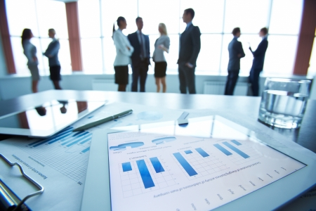 revisando documentos: Primer plano de documentos de negocios en touchpad tumbado en la mesa de trabajo, los trabajadores de oficina que interact�an en el fondo