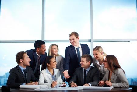 business smile: Grupo de socios de negocios discutiendo sus ideas a satisfacer
