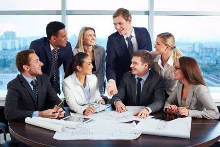 project: Group of friendly business partners discussing project at meeting