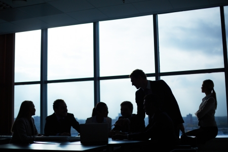 Several colleagues communicating in office against window photo
