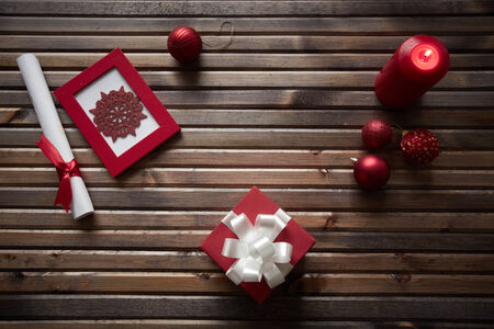 Image of red snowflake in frame, decorative toy balls, giftbox, burning candle and rolled paper wrapped with red silk ribbon on wooden background photo