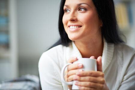 mujer tomando cafe: Retrato de joven morena con taza en las manos